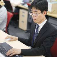 Kazuaki Hagiwara, who has a schizophrenic condition, works at Transcosmos Inc. in Shibuya Ward, Tokyo, in June. The outsourcnig service company actively hires people with mental health issues. | KYODO