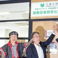 Iga Mayor Sakae Okamoto (left) and Mie University President Yoshihiro Komada (center) pose in front of the university's newly establish international ninja research center in Iga, Mie Prefecture, on July 1. | KYODO