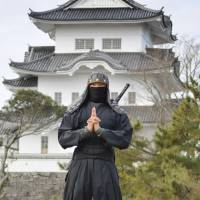 A man wearing a ninja costume has his photo taken with Ueno Castle in Iga, Mie Prefecture, in the background. A graduate school of Mie University is planning to introduce ninja studies as one its entrance exam subjects. | KYODO