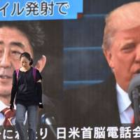 A woman walks in front of a huge television screen in Tokyo on Tuesday showing Prime Minister Shinzo Abe and U.S. President Donald Trump, following a North Korean missile test that overflew Japan. | AFP-JIJI