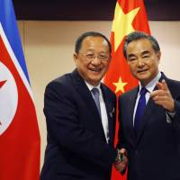 North Korean Foreign Minister Ri Yong Ho (left) is greeted by his Chinese counterpart, Wang Yi, prior to their bilateral meeting in the sidelines of the ASEAN Foreign Ministers' Meeting on Aug. 6 in Manila. | AP