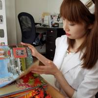 Online celebrity Chunhun, a leading voice among young women fascinated with North Korean culture, flips through a photo album of North Korean leader Kim Jong Un at the home of a like-minded friend in Tokyo on July 27. | TOMOHIRO OSAKI