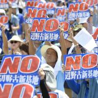Demonstrators hold up signs Saturday to protest the construction of a new U.S. military helipad off Nago, Okinawa Prefecture, during a rally in Naha, the capital. | KYODO