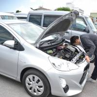 An exporter checks a used vehicle at a facility set up by Orix Auto Corp. in Tomigusuku, Okinawa Prefecture, on Aug. 1. | THE OKINAWA TIMES