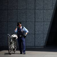 A police officer stands guard in Tokyo on July 31. | REUTERS