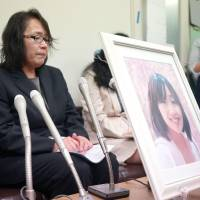 Mayumi Morishita holds a news conference Tuesday in Fukuoka after filing a lawsuit asking that the suicide of her daughter, Kana, be covered by workers' compensation. | KYODO