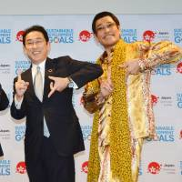 Piko Taro is seen with Foreign Minister Fumio Kishida and an unidentified woman at a promotional event for the U.N. Sustainable Development Goal at United Nations' headquarters in New York on July 17. | KYODO