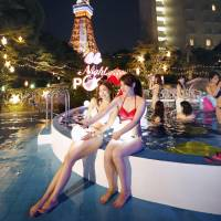 Women take a selfie by the pool at the Tokyo Prince Hotel on July 21. Young Japanese women are flocking to pools on summer evenings not so much to swim as to shine on social media. | KYODO
