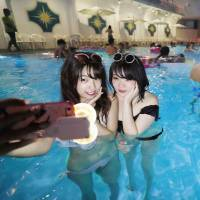 Two women take selfies at a night pool at the Hotel New Otani on July 21. | KYODO
