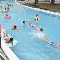 People swim in a pool at the Toshimaen amusement facility in Tokyo's Nerima Ward last week. KYODO