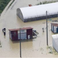 People wade through floodwaters in Daisen, Akita Prefecture, on Friday after torrential rain hit the Tohoku region earlier in the day. | KYODO