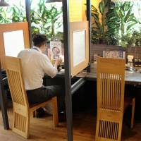 A man dines alone at a grilled meat restaurant in Fukuoka's Hakata Ward in June. Eateries that offer solo seating have become popular with office workers during lunch hours. | KYODO