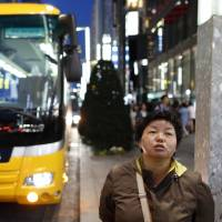 A Chinese tourist waits for a tour bus in Tokyo's Ginza district in April 2016. | BLOOMBERG