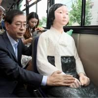 Seoul Mayor Park Won-soon touches the hand of a 'comfort woman' statue installed on a bus in Seoul on Monday. | SEOUL METROPOLITAN GOVERNMENT  / VIA KYODO