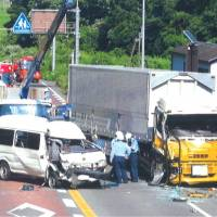 Police officers Wednesday investigate the scene of an accident involving a police van and a truck in Ogi, Saga Prefecture, that left a prisoner dead. | KYODO
