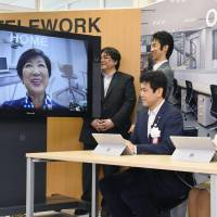 Tokyo Gov. Yuriko Koike appears on a monitor on July 24 while taking part in a nationwide campaign to promote telecommuting. | KYODO