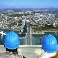 Tourists view the city of Kobe from the top of the Akashi Kaikyo Bridge in this undated handout photo from Honshu-Shikoku Bridge Expressway Co. | KYODO