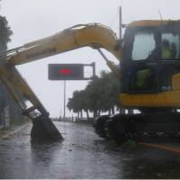 A digger is parked across a national highway in Nichinan, Miyazaki Prefecture, on Sunday to block access to it after the road was closed due to Typhoon Noru. | KYODO