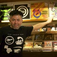 Not so dumb: Ryohey 'Nass' Nasu of So-Cho Pistons points to his band's album in Dumb Records, a record shop and bar he owns in Hiroshima's Naka Ward. | PETER CHORDAS