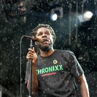 Jamaican singer Jamar McNaughton, better known as Chronixx, performs during a rain shower on the White Stage on Saturday. | JAMES HADFIELD