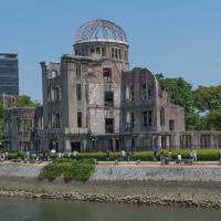 Unforgettable: Tourists pass the Atomic Bomb Dome in Hiroshima. | STEPHEN MANSFIELD