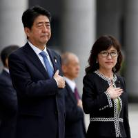 Prime Minister Shinzo Abe and then-Defense Minister Tomomi Inada review the honor guard before a meeting with senior members of the Self-Defense Forces' at the Defense Ministry in Tokyo last September. Inada announced her resignation on July 27. | REUTERS