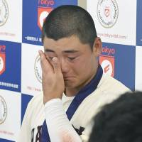Blubbering slugger: Kotaro Kiyomiya sheds tears after his team, Waseda Jitsugyo High School, was eliminated from the regional high school baseball playoffs on July 30 in Tokyo. Elimination means his team won't be heading to the finals, and Kiyomiya — a final-year student — may not get the chance to top the record for high school home runs he currently shares with another player. | KYODO
