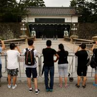 The perfect picture: Visitors observe the changing of the Imperial Guard officers at the Imperial Palace in Tokyo. Japan's top tourist destinations have seen a rise in visitors and in some cases their presence is impacting the lives of residents. | REUTERS