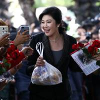 Ousted former Thai Prime Minister Yingluck Shinawatra greets supporters on Tuesday as she arrives at the Supreme Court in Bangkok, where she is on trial for negligence over a rice subsidy scheme that could see her imprisoned for up to 10 years. | REUTERS