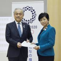 Tokyo Gov. Yuriko Koike receives a request from the Tokyo Medical Association calling for measures to prevent passive smoking on May 25. After the LDP postponed a smoking ban in June, Koike said she would step up efforts to make Tokyo smoke-free before the Olympics. | KYODO