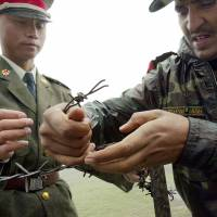 Chinese and Indian soldiers install a barbed wire fence at the Nathu La border crossing between India and China in India's Sikkim state in June 2006. On Monday, India and China said their troops were disengaging from a standoff on the Doklam plateau, a strategically important disputed territory in the area where the borders of  China and Bhutan meet. | AFP-JIJI