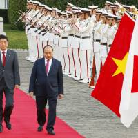 Vietnam's Prime Minister Nguyen Xuan Phuc, right, accompanied by his Japanese counterpart Shinzo Abe, center, reviews a guard of honor prior to their meeting at Akasaka Palace state guesthouse in Tokyo, Tuesday, June 6, 2017. (AP Photo/Shizuo Kambayashi)