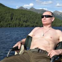 In a photo released by the Kremlin, Russian President Vladimir Putin is shown sunbathing during his vacation in the remote Tuva region in southern Siberia earlier this month. | AFP-JIJI