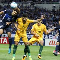 Japan's Yuya Osako (left) heads the ball away from Australia's Mathew Leckie as his teammate Trent Sainsbury looks on in the first half on Thursday. | AP