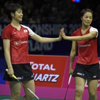 Japan's Yuki Fukushima (left) and Sayaka Hirota touch hands as they face China's Jia Yifan and Chen Qingchen in the women's doubles final at the World Badminton Championships on Sunday in Glasgow, Scotland. | AFP-JIJI