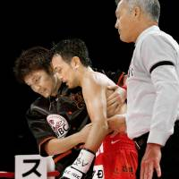 Shinsuke Yamanaka (center) suffered the first loss of his pro career on Tuesday. He fell to 27-1. | KYODO