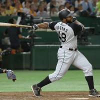 The Tigers' Jason Rogers strokes a two-run double in the second inning against the Giants on Saturday night at Tokyo Dome. Hanshin beat Yomiuri 8-4. | KYODO