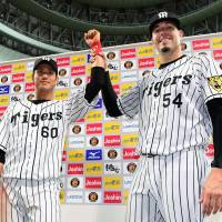Hanshin pitcher Randy Messenger (right) and outfielder Masahiro Nakatani celebrate after the Tigers' 3-0 win over Tokyo Yakult on Friday at Kyocera Dome in Osaka. | KYODO
