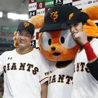 Giants pitcher Tomoyuki Sugano (left) and outfielder Daikan Yoh pose with team mascot Giabbit after Yomiuri's 8-2 win over the Dragons on Saturday at Tokyo Dome. | KYODO