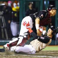 Eagles catcher Motohiro Shima (left) tags outs the Fighters' Hiromi Oka during the ninth inning on Wednesday night in Sendai. The Eagles won 6-5. | Kyodo