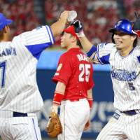 The BayStars' Toshihiko Kuramoto celebrates his walk-off single with teammate Takehiro Ishikawa on Thursday night at Yokohama Stadium. Yokohama defeated the Hiroshima Carp 5-4. | KYODO