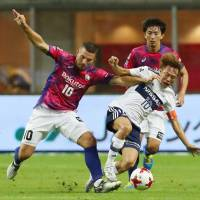Vissel Kobe's Lukas Podolski (left) and Yokohama F. Marinos' Manabu Saito compete for the ball during their 0-0 draw in the J. League on Sunday. | KYODO