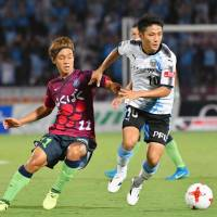 Ventforet's Yuki Horigome (left) and Frontale's Ryota Oshima compete during Sunday's match in Kofu. The teams settled for a 2-2 draw. | KYODO