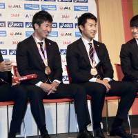 (From left) Japanese sprinters Kenji Fujimitsu, Yoshihide Kiryu, Shota Iizuka and Shuhei Tada take questions from reporters after the national team returned home from the IAAF World Athletics Championships at Haneda airport on Tuesday. They captured a bronze medal in the men's 4x100-meter relay in London. | KAZ NAGATSUKA