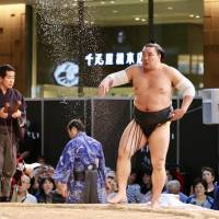 Yokozuna Harumafuji purifies the ring by tossing salt on it during Sunday's KITTE tournament. | KAZ NAGATSUKA