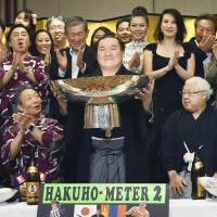 Hakuho celebrates after his victory in the Nagoya Grand Sumo Tournament in July. | KYODO