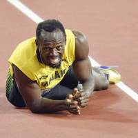 Usain Bolt lies on the track after injuring his leg during the 4x100-meter relay final at the world championships on Saturday.   KYODO