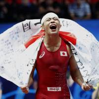 Kenichiro Fumita celebrates after beating Kazakhstan's Mirambek Ainagulov to win the men's Greco-Roman 59-kg gold medal at the world wrestling championships in Paris on Tuesday. | AP