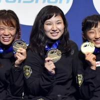Winners (from left) Risako Kawai, Sara Dosho and Yui Susaki pose Thursday after winning gold medals in the world wrestling championships in Paris. | KYODO