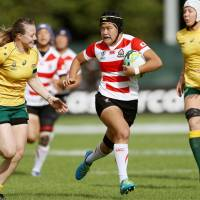 Japan's Riho Kurogi carries the ball as Australia's Samantha Treherne (left)  attempts to make a tackle in a  Women's Rugby World Cup Pool C match in Dublin on Thursday. | GETTY / VIA KYODO